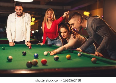 Group of friends play billiards at night out