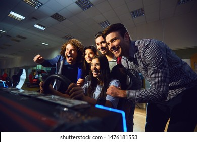 A group of friends playing arcade machine.