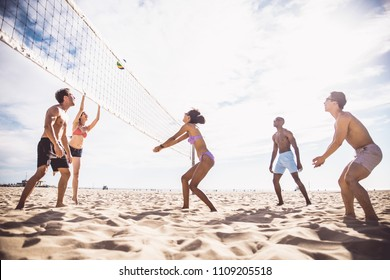 Group of friends playing beach volley - Multi-ethic group of people having fun on the beach