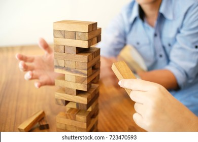 Group of Friends playing blocks wood game on the table folded puzzle