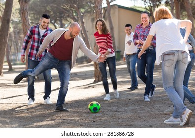 Group of friends playing football at picnic lunch. Selective focus