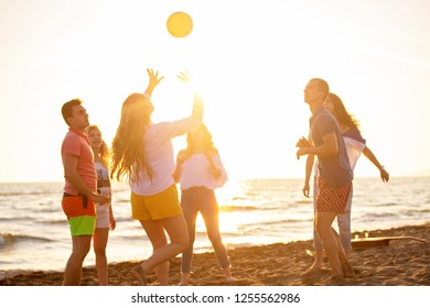 Group of friends playing game with ball at the beach on background of sunset sea