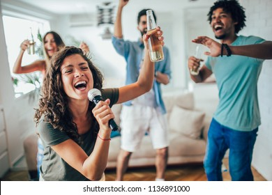Group of friends playing karaoke at home. Concept about friendship, home entertainment and people, selective focus