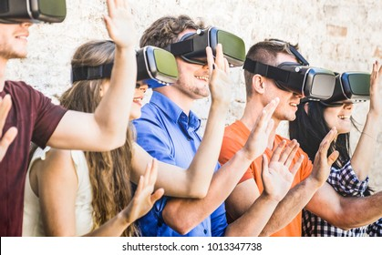Group of friends playing on vr goggles outdoors - Virtual augmented reality and wearable tech concept with young people having fun together with headset - Digital generation trend - Warm bright filter