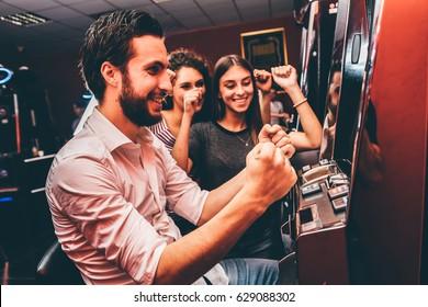Gruppe von Freunden, die Slotmaschinen spielen