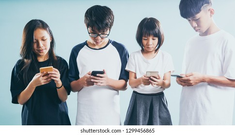 Group of friends playing smart phones .Concept of teenagers or youth addiction to new technology and social app trends .