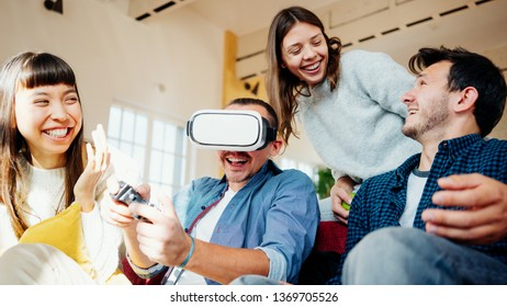Group of friends playing video computer games and fooling at home together. Using controller and VR helmet in big bright apartment