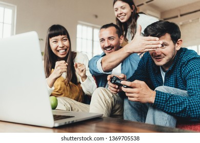 Group of friends playing video games and fooling at home together using controller in big bright apartment