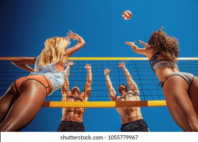 A group friends playing volleyball on the beach.