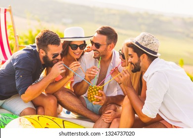 Group of friends at a poolside summer party, sitting at the edge of a swimming pool, drinking a pineapple cocktail and having fun