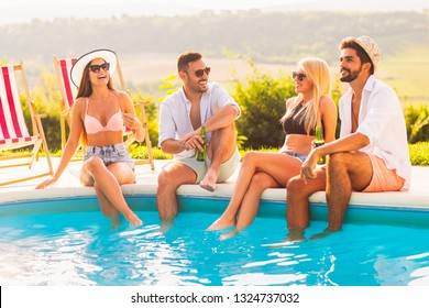 Group of friends at a poolside summer party, sitting at the edge of a swimming pool with legs in the water, drinking beer and having fun