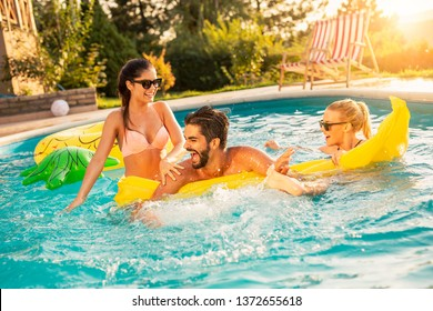 Group of friends at a poolside summer party,  having fun in the swimming pool, splashing water and fighting over a floating mattress