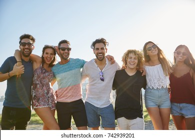 Group of friends posing together outside laughing