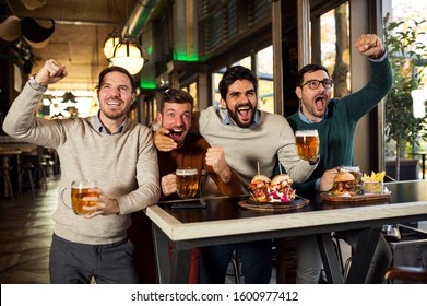 Group of friends in pub drinking beer and watching sport match
