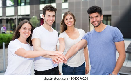 Group of friends putting their hands together, friendship concept
