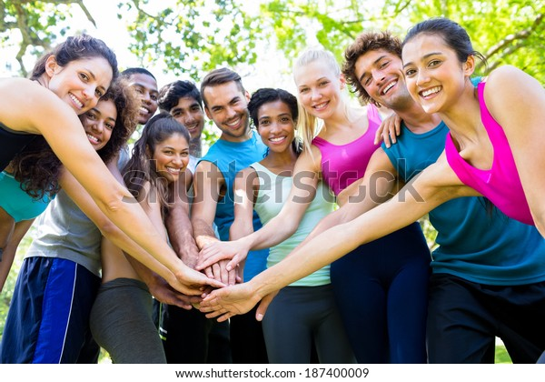 Group of friends putting their hands together in the park