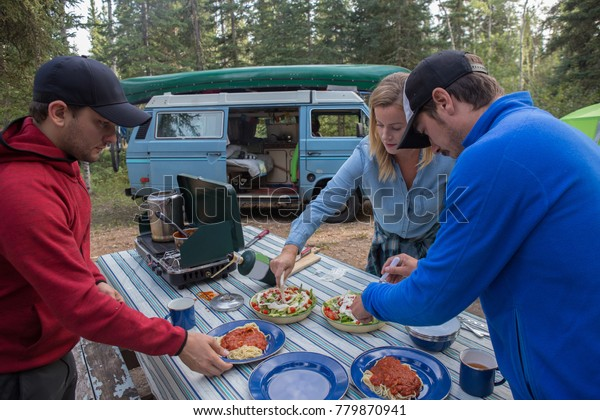 A group of friends relax around the campsite while living vanlife