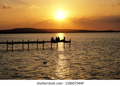 group of friends relaxing on pier watching sunset at lake Steinhuder Meer in Germany, unrecognizable people in silhouette