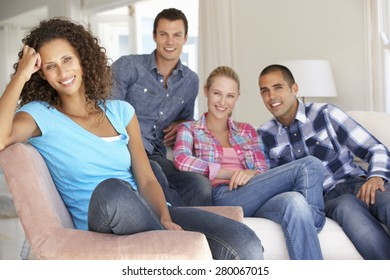 Group Of Friends Relaxing On Sofa At Home Together