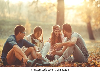 Group of friends relaxing the park on beautiful autumn day. Sitting on ground and making fun.
