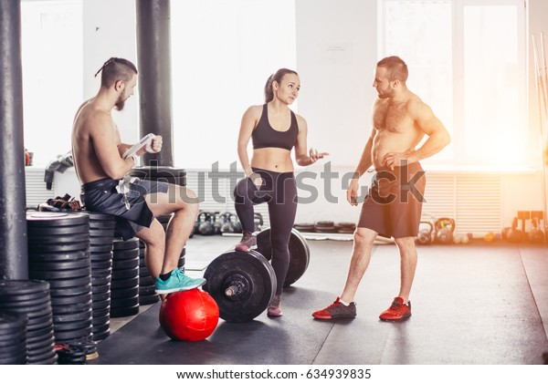 Group of friends relaxing and taking a break after working out at a cross-training gym