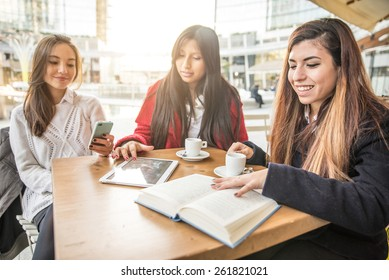 Group of friends at restaurant drinking coffee - Women with books,tablets and smart phone - Concepts about technology,communication and youth culture