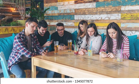 Group of friends at restaurant ignoring each other in favour of mobile phone - Young people addicted by mobile phone on social network - Connected millennials interacting with smartphones always onlin