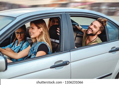Group of friends riding in the car with open windows and laughing