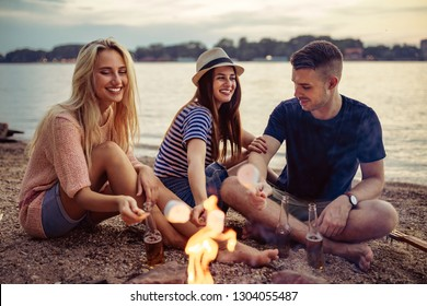 Group of friends roasting marshmallows over campfire