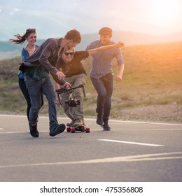 Group of friends run, laugh and shoot with the camera on the electronic suspension, the guy the longboard