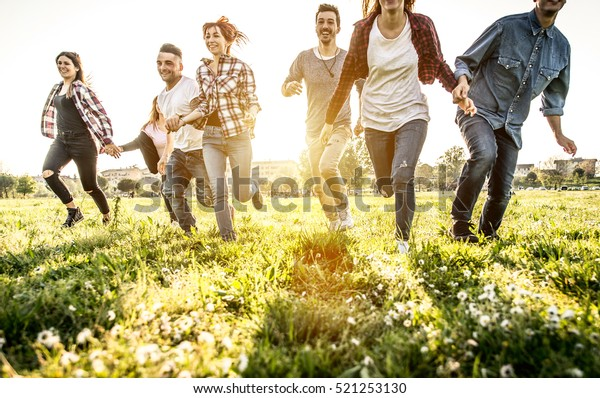 Group of friends running happily together in the grass