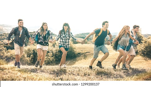 Group of friends running on grass meadow on country side - Happy friendship and freedom concept with young millenial people moving free at camping experience - Vintage desaturated filter