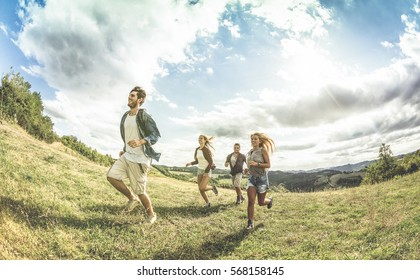Group of friends running on grass meadow - Friendship and freedom concept with young happy people moving free at camping experience - Vintage desaturated filter with backlight contrast sunshine