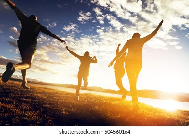 Group of friends runs to sunset. Togetherness concept