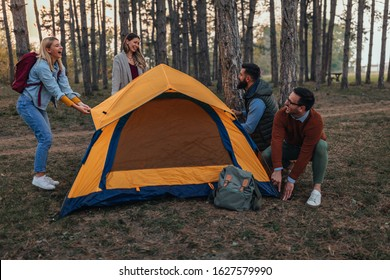 Group of friends setting up a tent while camping in the wilderness