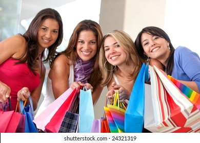 group of friends shopping in a mall holding some bags