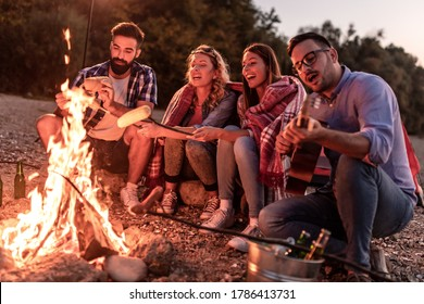 Group of friends sitting around the fire at night, having great time on the beach.