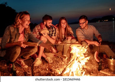 Group of friends sitting around the fire at night, grilling sausages and having great time on the beach.