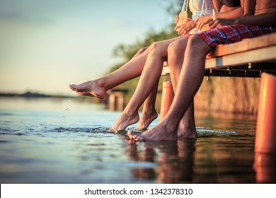 Group of friends sitting and having fun on the pier by the lake on sunset.Only legs are visible.