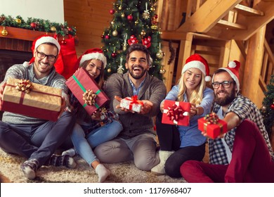 Group of friends sitting next to a fireplace and a nicely decorated Christmas tree, having fun on Christmas morning, exchanging Christmas presents