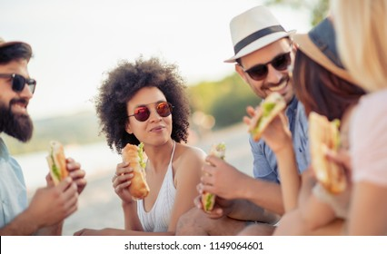 Group of friends sitting on the beach and eating sandwiches during picnic.