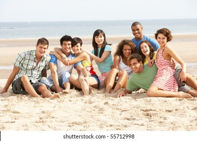 Group Of Friends Sitting On Beach Together