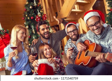 Group of friends sitting on the floor next to a nicely decorated Christmas tree, playing the guitar, singing Christmas songs and drinking wine