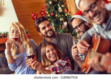 Group of friends sitting on the floor next to a nicely decorated Christmas tree, playing the guitar, singing Christmas songs and drinking wine. Focus on the couple on the left