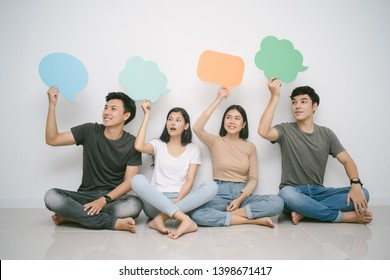 Group of friends sitting on the floor looking sideways while holding up speech bubble icons