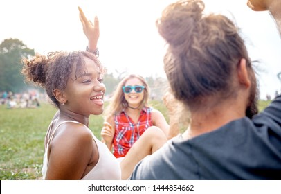 Group of friends sitting on grass and having fun at summer music festival