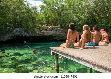 Group of friends sitting on jetty at cenote Azul in Mexico