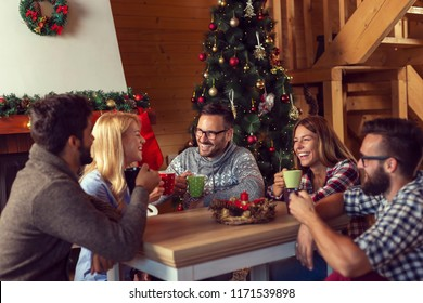 Group of friends sitting on the living room floor next to a Christmas tree and a fireplace on a Christmas morning, drinking coffee and having fun. Focus on the guy in the middle