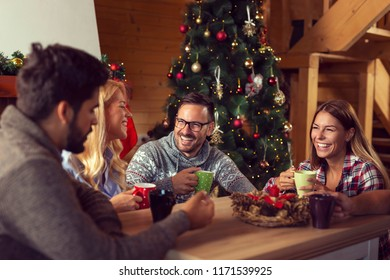 Group of friends sitting on the living room floor next to a nicely decorated Christmas tree on a Christmas morning, drinking coffee and having fun