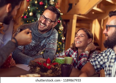 Group of friends sitting on the living room floor next to a Christmas tree and a fireplace on a Christmas morning, writing a letter to Santa and having fun. Focus on the couple in the middle